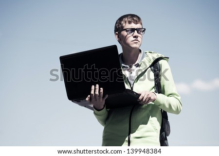 Young man holding laptop against a sky - stock photo