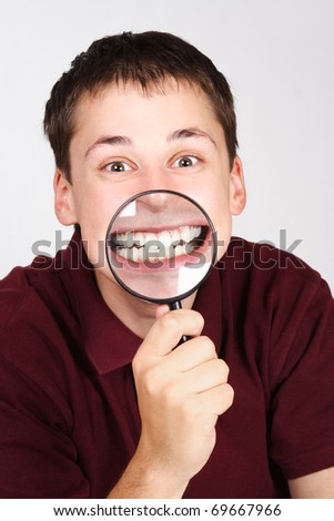 young man holding magnifier and showing teeth through it - stock photo
