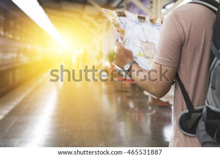 young man holding map with backpack standing on platform at train station - travel concept