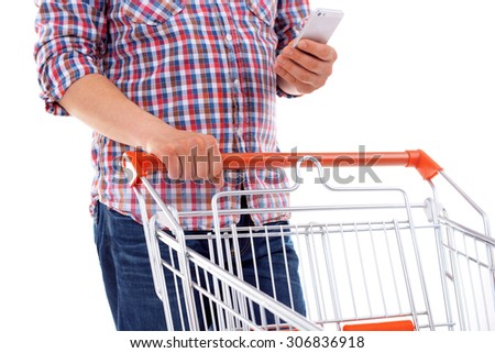 Young man holding mobile phone and shopping cart isolated on white