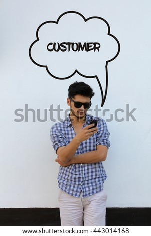 Young man holding mobile phone writen Customer on it - stock photo