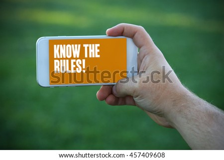 Young man holding mobile phone writen Know The Rules! on it - stock photo
