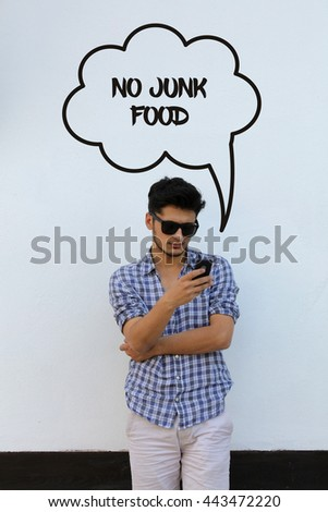 Young man holding mobile phone writen No Junk Food on it - stock photo
