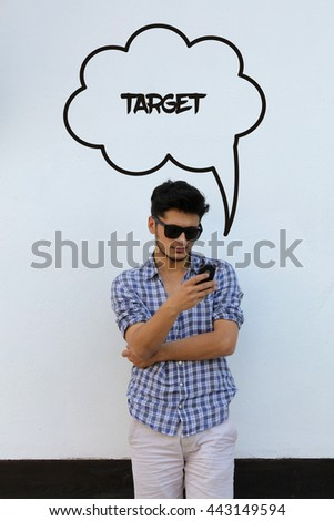 Young man holding mobile phone writen Target on it - stock photo