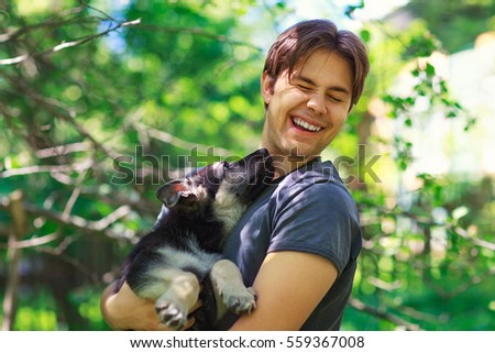 Young man holding on hands and playing with dog summer portrait