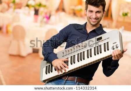 Young Man Holding Piano, Indoor - stock photo