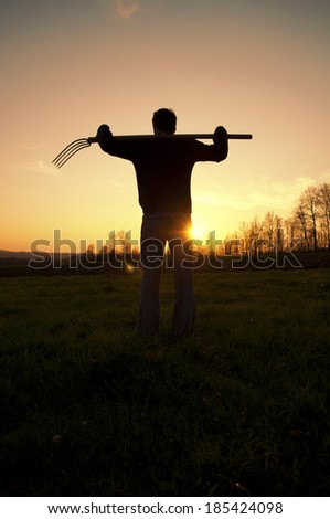 Young man holding pitchfork  - stock photo