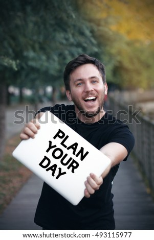 Young man holding Plan Your Day sign
