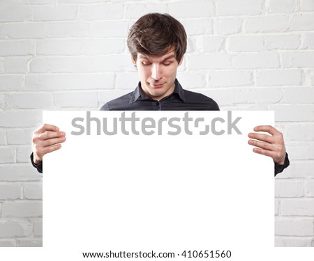 young man holding poster in brick room - stock photo