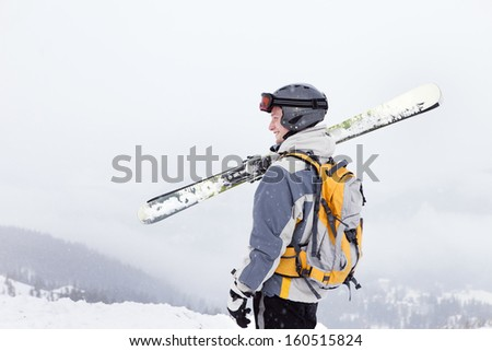 Young man holding ski, he looking away and smiling, copy space, close-up
