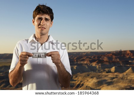 Young man holding small one dollar bill - stock photo