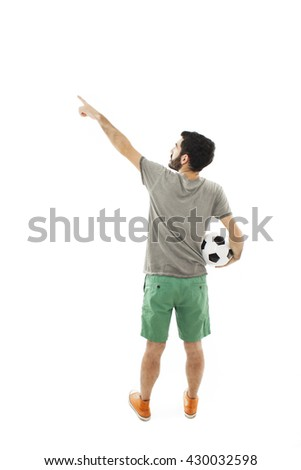 Young man holding soccer ball, pointing. Rear view. Isolated on white background - stock photo