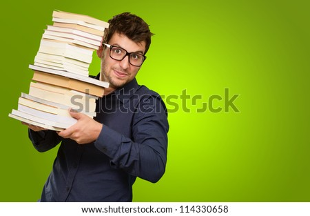 Young Man Holding Stack Of Books On Green Background - stock photo