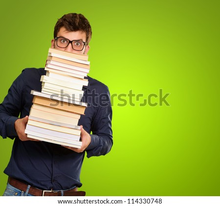 Young Man Holding Stack Of Books On Green Background