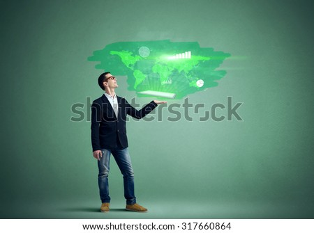 Young man holding tablet with flying social networking icons on green background