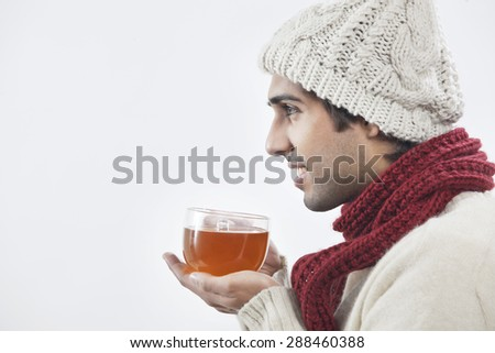 Young man holding tea cup over white background