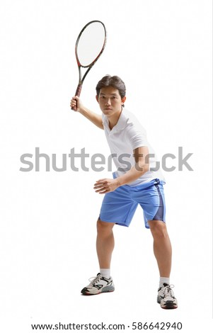 Young man holding tennis racket, waiting