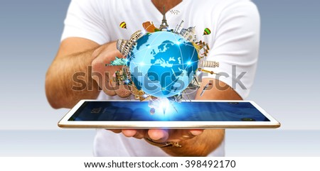 Young man holding the planet earth surrounded by famous monuments of the world over his digital tablet - stock photo