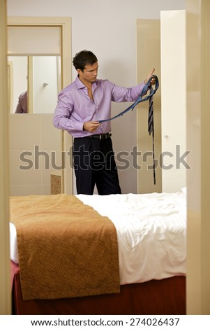 Young man holding tie in hotel room