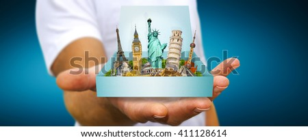 Young man holding travel box in his hand containing famous monuments of the world - stock photo