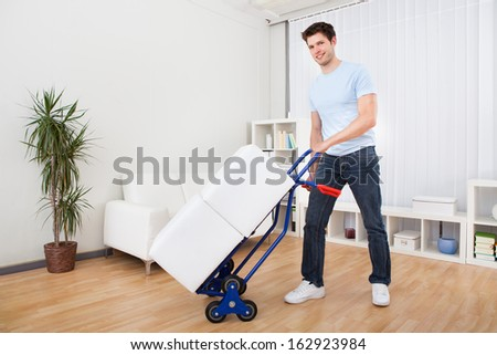 Young Man Holding Trolley Loaded With Cardboard Box - stock photo