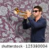 Young Man Holding Trumpet On Wallpaper - stock photo