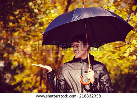 Young man holding umbrella at autumn day - stock photo