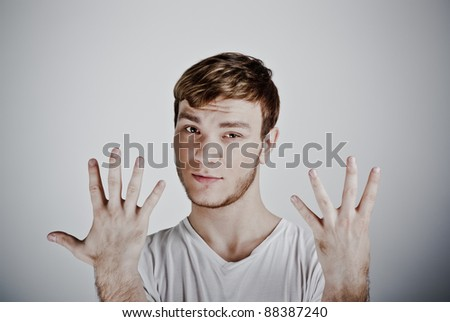 young  man holding up ten fingers - stock photo