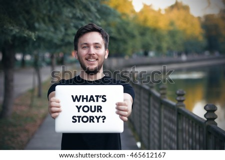 Young man holding  Whatâ??s Your Story? sign