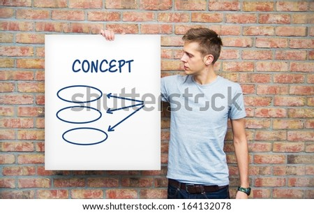 Young man holding whiteboard with diagram - stock photo