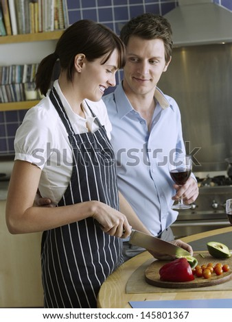 Young man holding wineglass while looking at woman chopping vegetables at kitchen counter