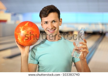 Young man holds orange ball and bottle with water in bowling club; shallow depth of field - stock photo