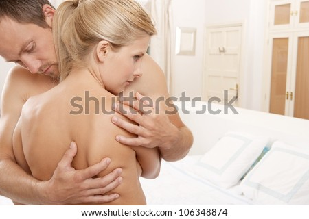 Young man hugging a nude woman in a bedroom. - stock photo