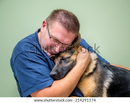 Young man hugging and consolating his dog - stock photo
