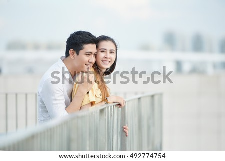 Young man hugging his girlfriend from behind