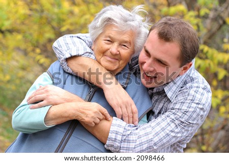 Young man hugging senior woman