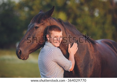 Young man hugs a horse. Autumn outdoors scene - stock photo