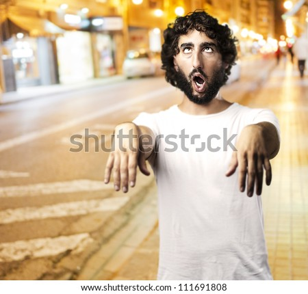 Young man imitating a zombie against a city at night background