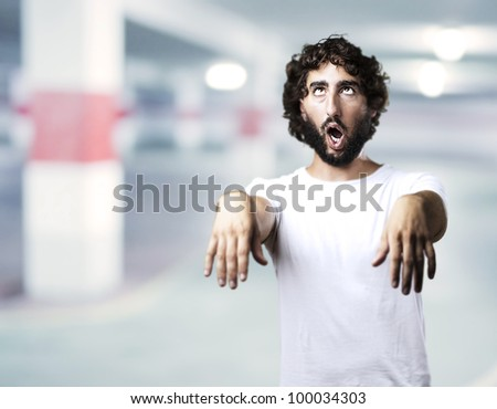 young man imitating a zombie against a garage background