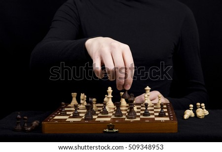 young man in a black jacket transposes a pawn on a wooden chess board against a black background