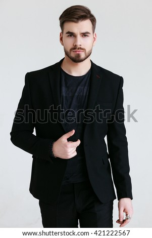 young man in a black suit on a grey background
