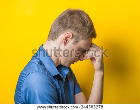 Young man in a blue shirt on a yellow background. showing fatigue two hand under head, anger, misunderstanding. gesture. photo shoot. - stock photo