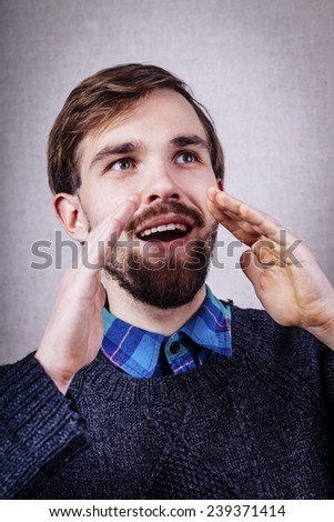 young man in a blue sweater says something loud - stock photo