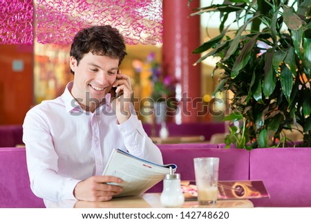 Young man in a cafe or ice cream parlor reading a magazine and using his phone, maybe he is single or waiting for someone - stock photo