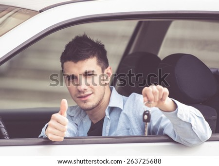young man in a car showing his car keys - stock photo