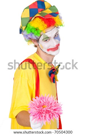 Young man in a clown's costume holding a pink flower - isolated