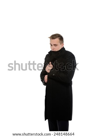 Young man in a coat. Distrust in oneself context.  Copy space on the left is for your text .  - stock photo