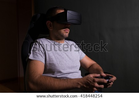 Young man in a dark room wearing virtual reality glasses and playing a videogame using a remote controler. - stock photo