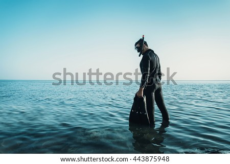 Young man in a diving suit with a mask and flippers goes to the sea in summer outdoor - stock photo