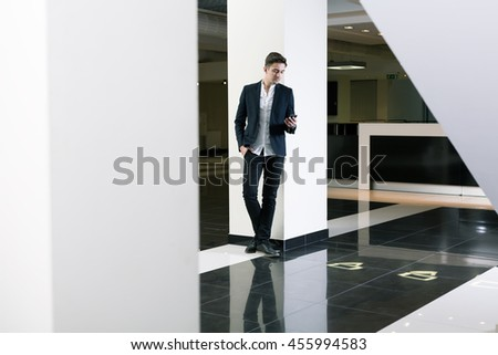 Young man in a hall of a modern public building, using his mobile phone